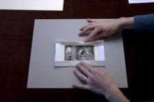 1. Corta un trozo de papel más grande que la obra, al menos, 2,5 cm en todos los bordes. Dobla el papel alrededor de la obra.