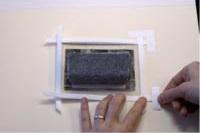 7. Coloca la obra en la trasera y fíjala usando cinta de papel o lino con adhesivo al agua.