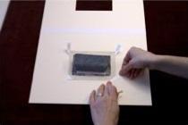 3. Marca la posición de las esquinas superiores con un papel pero no las pegues aún. Asegura las esquinas inferiores en su sitio usando cinta con adhesivo al agua de papel o lino. Retira la obra.