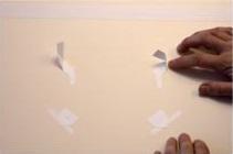 4. Fija las esquinas superiores en un solo lado usando cinta adhesiva. Estas esquinas pueden ser liberadas para retirar la obra.